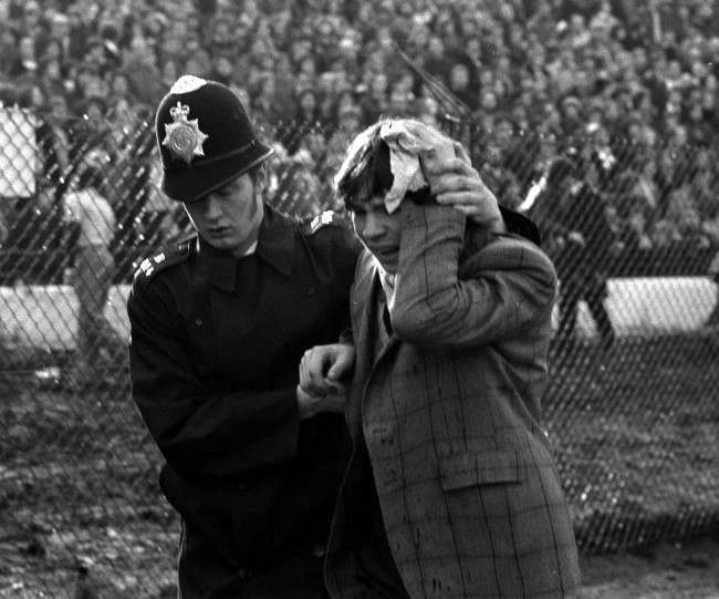 Police in Action at Chelsea. A Policeman escorts a young fan nursing an injured head at Stamford Bridge, where rioting spectators spilled over the barriers before the start of Chelsea's League Division Two promotion battle against London rivals Millwall. Date: 12/02/1977
