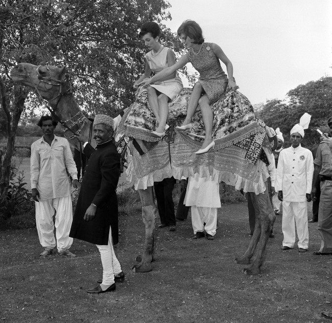 First lady Jacqueline Kennedy, right, goes for a camel ride, side saddle in a tight skirt in Karachi, Pakistan, March 25, 1962. Seated beside her is her sister Princess Lee Radziwill. Leading the camel is Bashir Ahmad, who visited the U.S. in 1961 as the guest of Vice President Johnson.