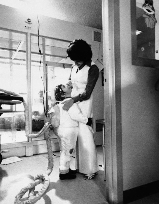 "Little David Vetter, the six-year-old ""bubble baby"", gives his mother Carol Ann Vetter, a hug while wearing his new Mobile Isolator System, in Houston, Nov. 4, 1977. David suffers from Severe Combined Immune Deficency Syndrome (SCIDS) The suit is a germ-free space type suit that enables David to leave his germ-free bubble that he has lived in since birth. The long hose attached to David's back is a live-support system that pumps air into the suit. ("