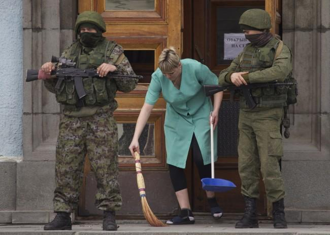 A woman sweeps away the broken glass as two unidentified armed men guard the entrance to the local government building in downtown Simferopol, Ukraine, on Sunday, March 2, 2014. A convoy of hundreds of Russian troops headed toward Simferopol the regional capital of Ukraine's Crimea region on Sunday, a day after Russia's forces took over the strategic Black Sea peninsula without firing a shot.