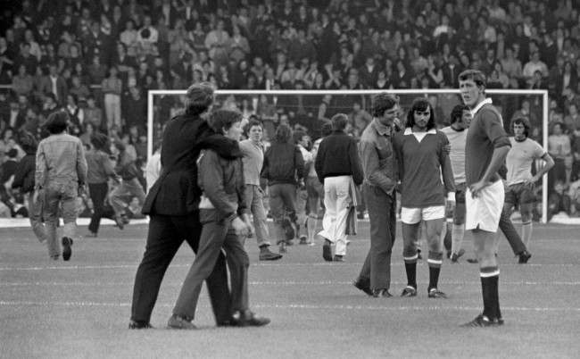 A policeman gets a neck hold on a youth at Anfield, where hundreds of youngsters were invading the pitch just before the start of the First Division match between Manchester United and Arsenal. But over on the right, a fan consoles United star George Best, who was sent off in the match at Chelsea. Manchester United were banned from playing at home for the first two games of the season following hooliganism at Old Trafford the previous season. Ref #: PA.1997120  Date: 20/08/1971