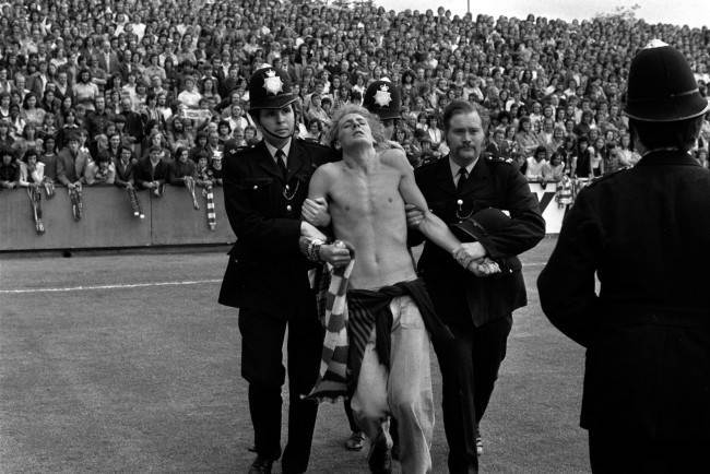 Stripped to the waist, a man is led away by police at Brisbane Road ground before the League Division Two match between Orient and Manchester United on the opening day of the 1974/75 season. Date: 17/08/1974