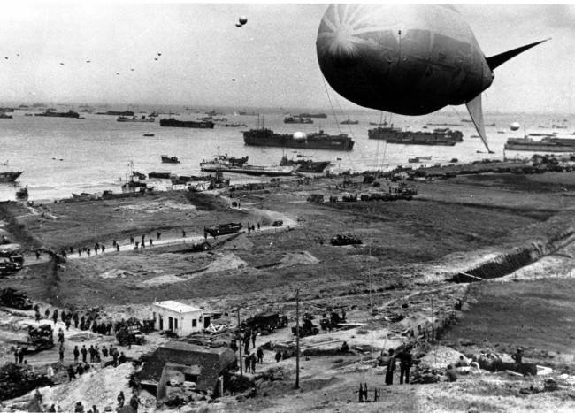 "Allied materials of war, including amphibious ""ducks"" and other armored vehicles, fills an invasion beach on the Normandy coast of France, protected by barrage balloons during World War II. The balloons also hover over ships anchored off shore waiting their turn to unload the reenforcement supplies June 18th, 1944"
