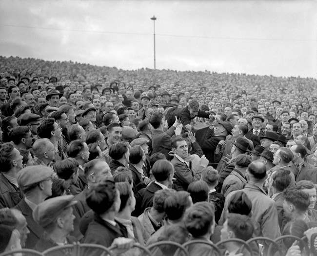 PA. 2814930 Soccer - Football League Division One - Chelsea v Arsenal - Stamford Bridge A young fan is passed over the heads of the crowd to a better viewing position at the front of the terrace Date: 01/11/1947