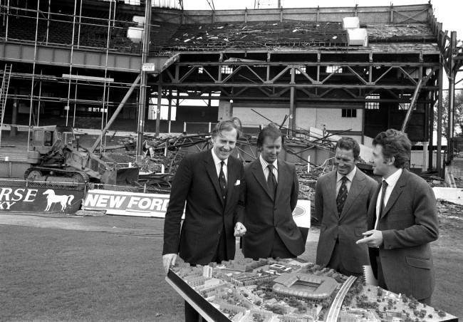 (L-R) Roger Bannister, Chelsea chairman Brian Mears, Chelsea manager Dave Sexton and architect John Darbourne examine a model of the proposed new developments at Chelsea's Stamford Bridge home, whilst demolition of the old stands continues in the background Ref #: PA.2935316  Date: 05/06/1972