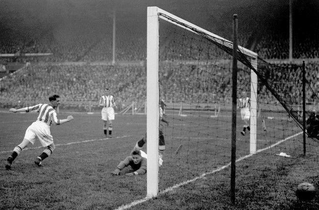 Huddersfield Town goalkeeper Hugh Turner (c) is beaten by Arsenal's first goal, scored by Alex James (not in pic)