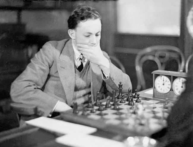 While their athletic comrades were disputing on the track at the White City, chess teams representing Oxford and Cambridge met in a chess match at the City of London Chess Club. GP Britton of Oxford is shown pondering his next move in his match against Cambridge's DB Schultz