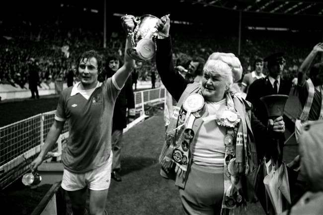 Manchester City's Asa Hartford (l) and famous fan Helen 'The Bell' Turner parade the League Cup around Wembley after their 2-1 victory