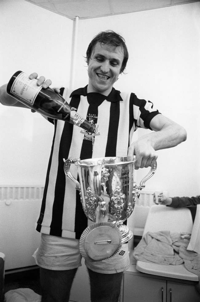 Manchester City's winning goalscorer Dennis Tueart, wearing a Newcastle United shirt, celebrates victory in the changing rooms after the match