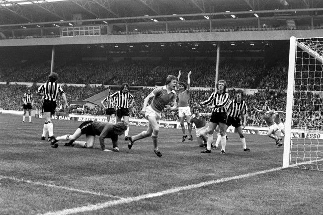 Manchester City's Peter Barnes (c) celebrates scoring the opening goal, much to the disappointment of the Newcastle United defence
