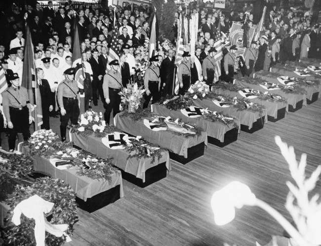 Funeral services for the 28 Germans who lost their lives in the Hindenburg disaster May 6 are held on the Hamburg-American pier in New York City. The swastika-draped caskets will be placed on board the Hamburg for their return to Europe. About 10,000 members of German organizations line the pier.