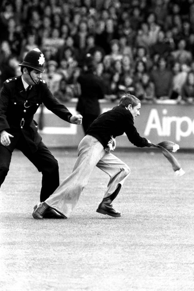 Soccer - Football League Division Two - Orient v Manchester United A Manchester United fan is chased by a policeman NULL Ref #: PA.398281 Date: 17/08/1974