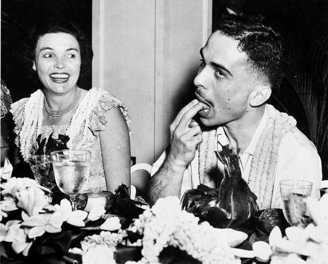 23-year-old King Hussein of Jordan tries a native Hawaiian dish at a feast given by Gov. William F. Quinn, as the governor's wife, Nancy, looks on. Hawaii, March. 19, 1959.