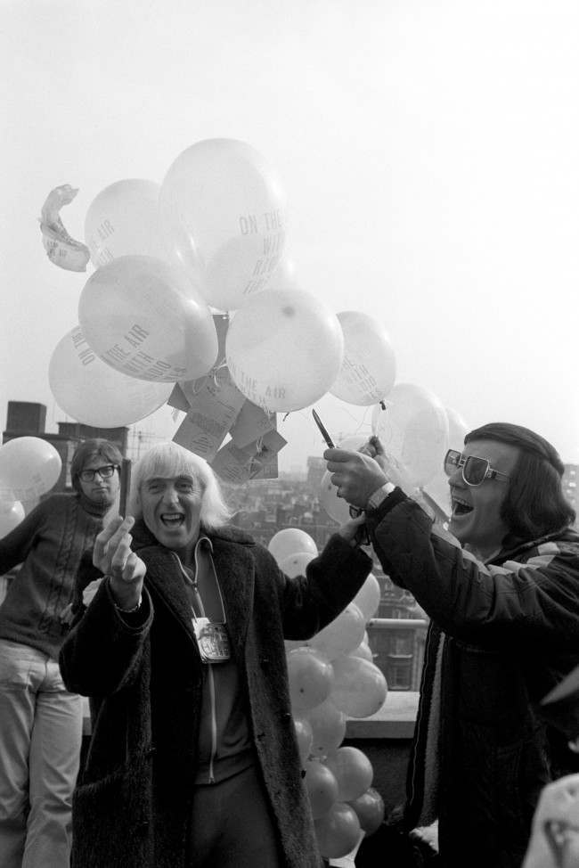 (L-R) Radio One disc jockeys Jimmy Savile and Alan Freeman threaten to burst the balloons which were to be launched from the roof of Broadcasting House to celebrate the fifth anniversary of the station Date: 29/09/1972