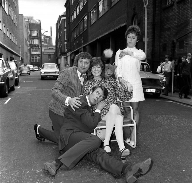 Leslie Crowther (second l) listens for the heart beat of Cilla Black's unborn child, assisted by Terry Scott (l), Basil Brush, who is looking over Cilla's shoulder, and Sheila Burnette, who is checking Cilla's pulse. Date: 06/07/1970