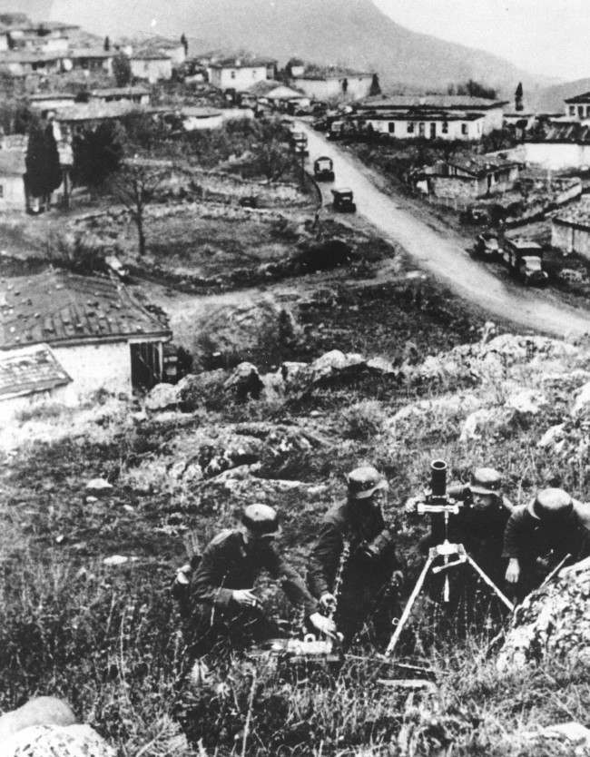 As the German invasion of the southern Ukraine continues, soldiers of an advance division are seen at an unknown village, somewhere between the Crimean Mountains and the Black Sea, on March 12, 1941. A military convoy is moving down a street in the background.