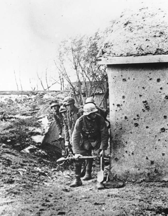 As the German invasion of the Ukraine continues, soldiers of the invading Wehrmacht troops are seen in the cover of a shell-marked wall, at an unknown location on the Crimean peninsula, in November 1941.