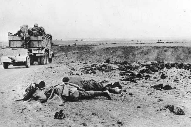 The bodies of two fallen Soviet soldiers lie at roadside, while a truck of the Romanian Army, with an artillery gun in tow, advances towards the city of Kerch, in June 1942, during the Battle of the Crimea in World War II.