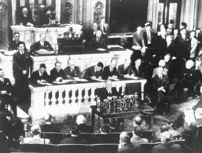 Sitting before a battery of microphones, U.S. President Franklin D. Roosevelt reports to Congress, Washington, DC, March 1, 1945, on the Crimea Conference, between Roosevelt, Britain's Prime Minister Winston Churchill and Soviet Premier Joseph Stalin, which took place in February at Yalta, Russia. At extreme upper left is U.S. Vice President Harry S. Truman.