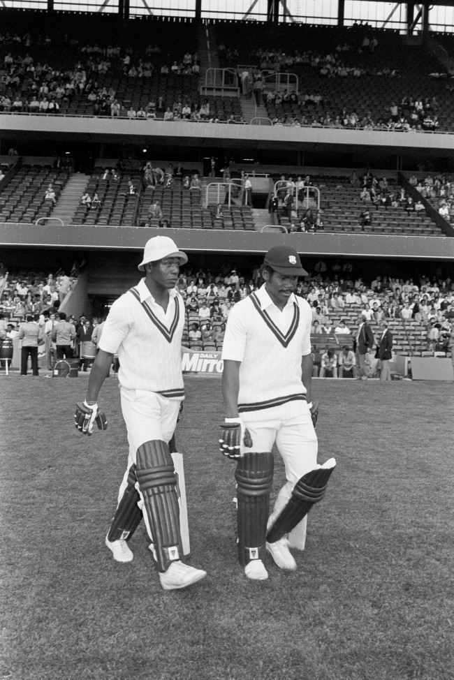 Cricket - Essex v West Indies - Day-Night Floodlit Match - Stamford Bridge Desmond Haynes (l) and Gordon Greenidge (r) of the West Indies walk out to the crease. The floodlit cricket match at Chelsea Football Club's ground, Stamford Bridge, was the first in England, as pioneered by the Packer Circus in Australia. The batsmen wear dark pads and gloves and the bowlers use a white ball. Archive-PA193552-1c Ref #: PA.4836613