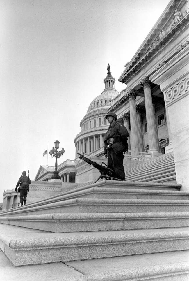 Troops, one with a machine gun, stand guard on the steps of the U.S. Senate wing of the Capitol Building in Washington, D.C., April 5, 1968. Federal troops were called into the nation's capital by order of President Lyndon Johnson during a day of arson and looting following the assassination of Dr. Martin Luther King, Jr. in Memphis, Tenn., April 4. The flag is at half staff in tribute to the civil rights leader.