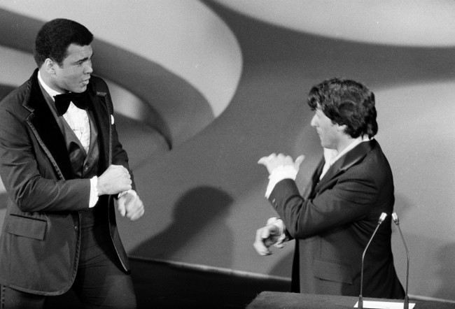 "Heavyweight boxing champion Muhammad Ali, left, makes a suprise appearance on the Academy Awards show, accusing actor Sylvester Stallone in jest of stealing ""my script"" and then sparring with Stallone, who wrote and starred in the boxing film ""Rocky,"" in Los Angeles, Calif., March 28, 1977. Stallone and Ali presented the award for best supporting actress."