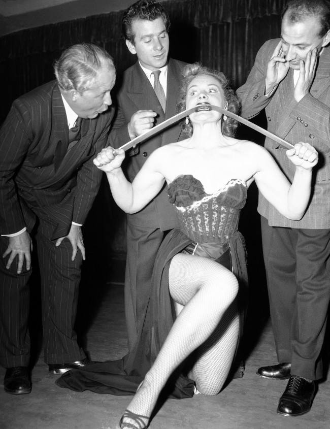 British strong woman, Joan Rhodes, demonstrates her strength and prowess by bending and iron bar with her bare hands and teeth for three interested men during her night club act Dusseldorf, Germany, Nov. 5, 1952. In Dec. 1955, Joan lifted comedian Bob Hope to her shoulders when Hope was in Iceland entertaining U.S. forces stationed there. Hope slipped from her grasp, hit the floor head-first and sustained a cut nose and injured neck. The following day he appeared on a British television show from London, after visiting a London doctor.