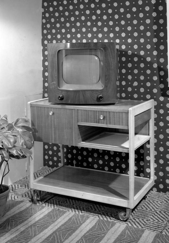 A television on a specially made trolley.