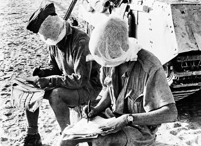 Members of a tank crew in the British forces in the Western Desert, in Egypt on Oct. 4, 1942, have to fight flies when they are not fighting the enemy. Soldiers writing home before a day's patrol wear mosquito netting masks.