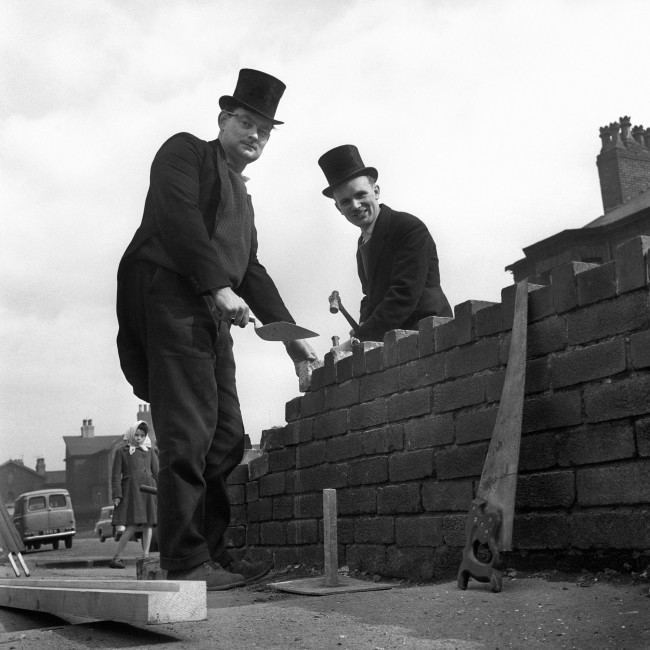 Wearing top hats and tails as they build a wall in Manchester are Malcolm West, 31, of Levenshulme, Manchester (left) and Colin Whittaker, 26, of Edgeley, Stockport, who run their own building business. Because they are 'fed up' with the working man always being associated with cloth caps and overalls, they go to work in morning dress (bought for five shillings) and toppers - and hope that other working men will follow suit.