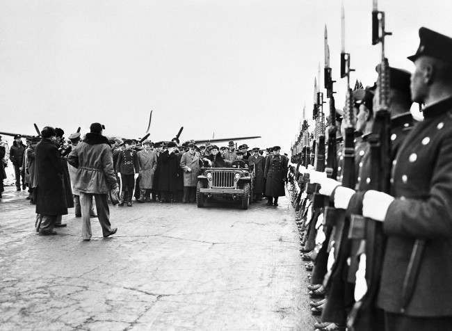 Riding in an American Jeep, President Franklin D. Roosevelt is greeted at the Airport in Yalta, Crimea, Russia, by Russian and British officials with a Russian honor guard at the right on Feb. 12, 1945. In the group at the left of the jeep are: Secretary of State Edward R. Stettinius, Jr. (light coat), Russian Foreign Secretary Vyacheslov Molotov (Arm upraised) and Prime Minister Winston Churchill of Great Britain (light uniform coat, beside the jeep).