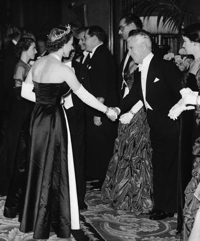 "Queen Elizabeth II shakes hands with actor Charles Chaplin during meeting in Empire Theatre, London, for the Royal Film Performance, a benefit performance to aid the Cinematograph Trade Benevolent Fund. At left in background is Princess Margaret and at extreme right is Mrs. Oona Chaplin. Others are not identified. The movie shown was ""Because You're Mine,"" marking first time that a musical from Hollywood had been chosen for this top British movie event. Chaplin, who was in London for recent premiere of his own new film, made a short appearance during hour-long stage show accompanying the movie presentation. Date: 27/10/1952"