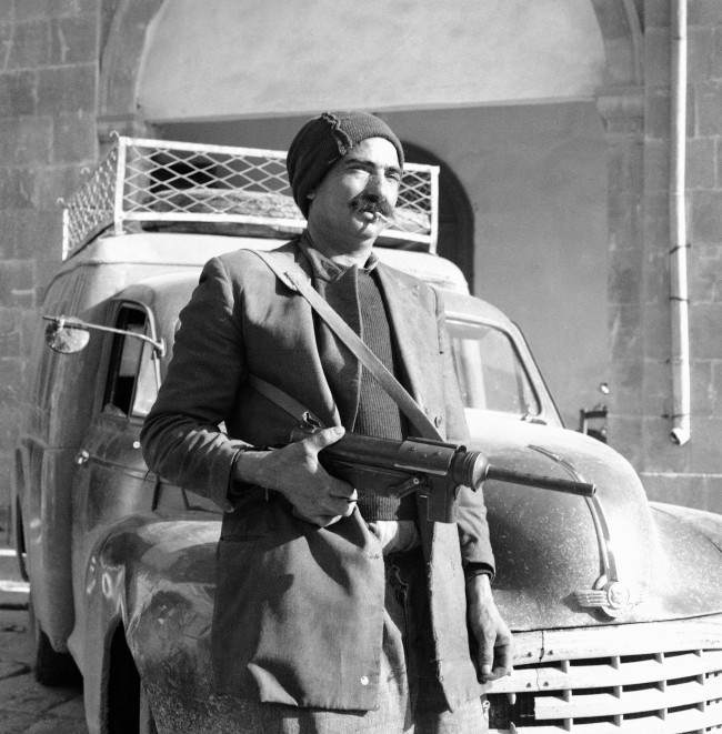 The Greek Cypriot Eoka Organization began handing in arms all over Cyprus, by the evening 613 rifles, guns and sub-machine guns, 17,000 rounds of ammunition, 2,000 bombs and a ton of explosive had been surrendered here, a Greek Cypriot poses with his Gun Outside Kykko monastery, near Nicosia, Cyprus, on March 13, 1959 as he arrived to hand it over to the Cyprus police yesterday.