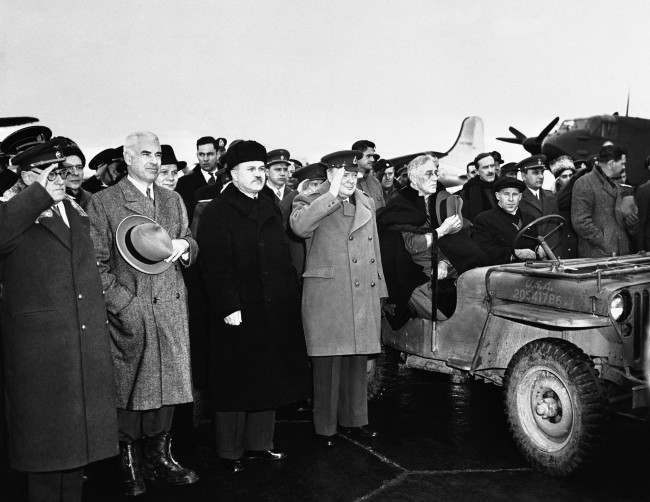 "President Franklin D. Roosevelt (right, hat over heart) is greeted at the airport at Yalta, Crimea, Russia, on Feb. 12, 1945, with the playing of the Russian Anthem as he met by Prime Minister Winston Churchill (in uniform beside the president) and Russian Foreign Secretary Vyacheslav Molotov (at left of Churchill) U.S. Secretary of State Edward R. Stettinius, Jr. is at the left of Molotov. The ceremony marked President Roosevelt's arrival for the ""Big Three"" conference."