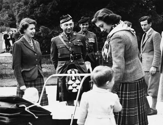 Group Captain Peter Townsend, right, watches Princess Margaret hold Prince Charles hand, at Berkhall, Deeside, Scotland on March 12, 1951. Princess Ann is in her pram, with the queen standing by. Senior members of the pipe band of the Argyll and Sutherland Highlanders of Canada, look on after playing for the royal party.