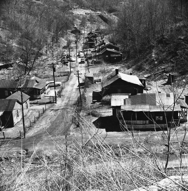 This is a community in Blue Grass Hollow not far from Hazard, Ky. March 29, 1962. It was formerly the mine camp of Blue Grass Mine which was, at one time, a big operation a big commissary, school and church. Now just the tar-paper roofed homes remain. The tipple is gone. The residents work small truck mines in the county when they can find work.