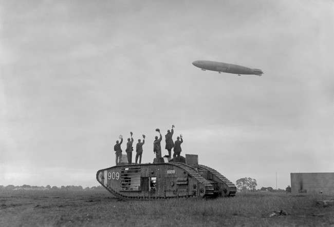 The Royal Navy Airship R34, returning from America to the aerodrome at Pulham, Norfolk, is cheered by British soldiers standing on a British Mark V tank. This was the first East-West crossing of the Atlantic and was done just two weeks after Alcock and Brown's first ever trans-Atlantic flight. Date: 13/07/1919