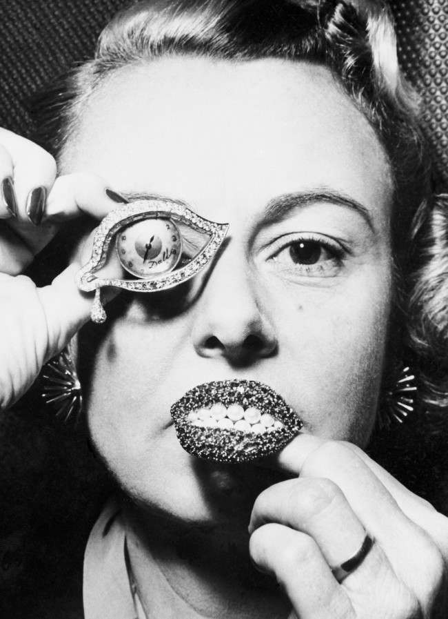Jewellery by Salvador Dali, a watch in the shape of an eye surrounded by diamonds and rubies, and a brooch of rubies in the shape of lips with pearls as teeth. Date: 08/11/1954