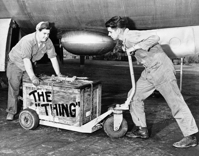 Sgt. R.M. McDaniel (left), of Chillicothe, Ohio, and S/Sgt. C.A. Christensen of Minot, N.D., get set to load ?The Thing? aboard a B-29 for special delivery along with bombs to the enemy? somewhere in Korea, March 13, 1951. The air force men belong to the U.S. Far East Air Forces? 19th bomb group.