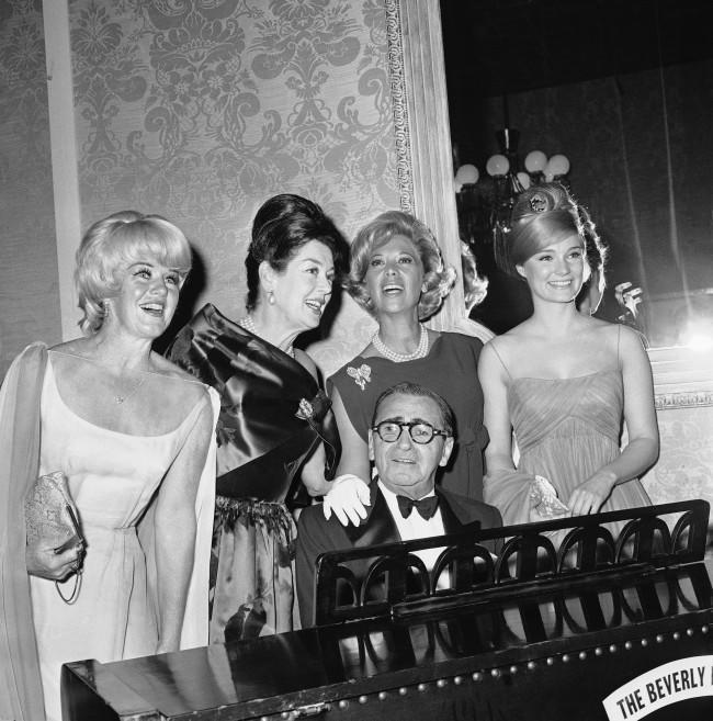 "Irving Berlin is joined by Ginger Rogers, Rosalind Russell, Dinah Shore and Yvette Mimieux, left to right, as the 75-year-old composer plays his well known ""Always,"" in Hollywood, March 5, 1963. The occasion was the big night for Berlin, staged by the Screen Producers Guild."