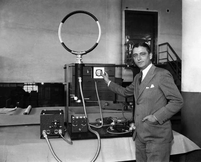 Geoffrey G. Kruesi, inventor from Woodside, NY is shown with his new radio compass, March 16, 1935. It is now being tested by the Department of Commerce in Oakland, California. Officials say the company manufacturing the compass is turning out 500 units for the U.S. Army. It is relieved that the new device which resembles a radio, may solve the problem of aerial navigation across the Pacific.