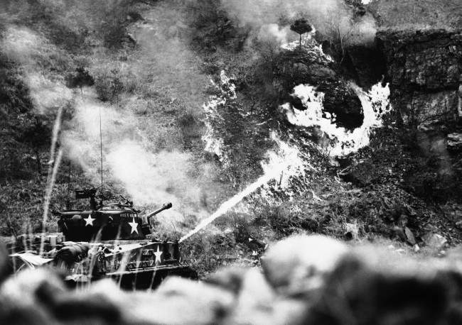 A 25th Division tank uses a flame thrower on an enemy pillbox deeply emplaced in a hillside near Korea?s Han River front on March 30, 1951. The scene is reminiscent of Pacific island warfare during World War II.