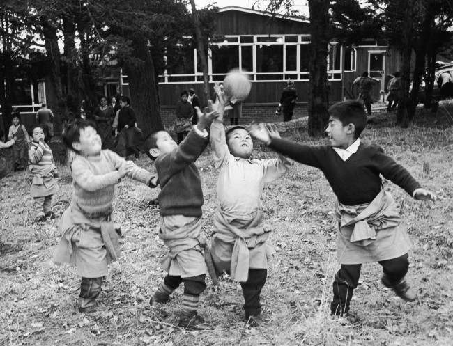 Four young Tibetan boys, some of the 21 Tibetan refugee children now settling in at the Pestalozzi children's village at Sedlescombe, near Battle, Sussex, England, enjoy a game of ball near their cedar wood house in the village on March 7, 1963. The children, who fled from the Chinese in 1956, are making new lives in Britain, after being specially nominated to come to this country by the Dalai Lama himself. He hopes they will be trained as doctors, teachers or in other skilled professions so they way eventually go back to their own land and help others less fortunate than themselves.
