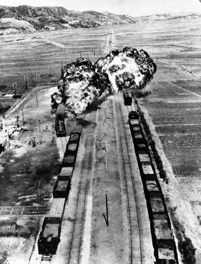 U.S. Fifth Air Force B-26 planes score a twin killing with direct hits on two enemy supply trains at Munchon, north of Wonsan on Korea?s east coast, March 30, 1951. Napalm bombs raise fiery balls of flame as the communist rail junction goes off schedule for some time to come.