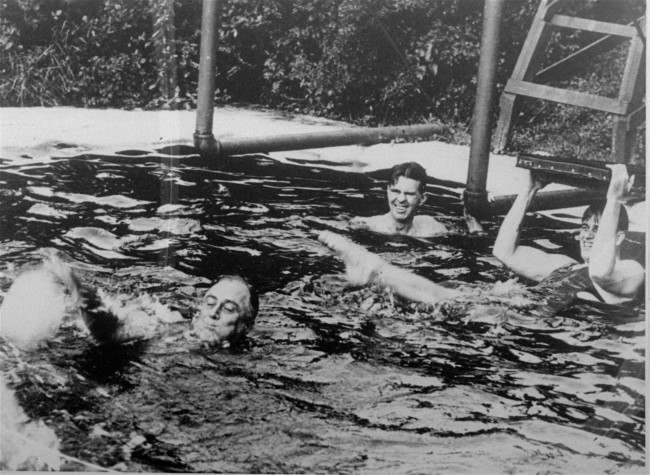 President Franklin D. Roosevelt is shown swimming in the pool of the Polio Foundation at Warm Springs, Georgia, March 31, 1935. FDR first went to Warm Springs, then the village of Bullochville, in the mid-1920's in an effort to swim his way to health in the warm waters. His visits paved the way for the foundation which became a center for the treatment of polio. During his last visit he broke ground for a new 90-bed wing.