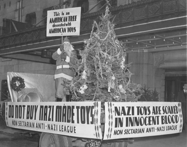 A Santa Claus on wheels appeared in front of a store in New York City on Dec. 6, 1938. The Santa bares signs urging the boycotting of Nazi Manufactured toys. A Christmas tree decorated with American toys shared the spotlight.