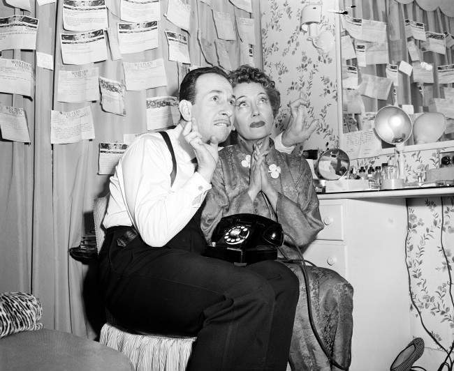 Oscar nominees Jose Ferrer and Gloria Swanson cross their fingers as they wait for news from Hollywood, where the Academy Awards are held, backstage at the Fulton Theater in New York City on March 29, 1951. Swanson is nominated for best actress