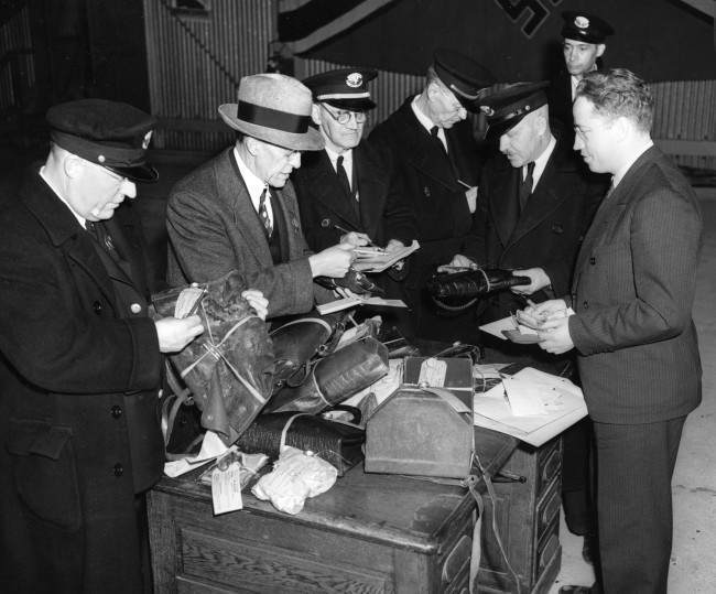 Customs officers search through baggage items salvaged in the Hindenburg explosion in Lakehurst, N.J., May 6, 1937.