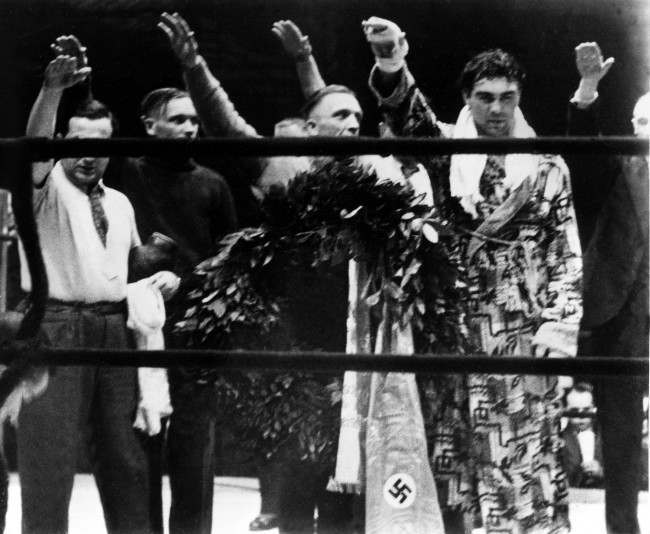 Max Schmeling, right, and his attendants give the Nazi salute after the German boxer defeated Steve Hamas in a boxing match in Hamburg, Germany, March 10, 1935.