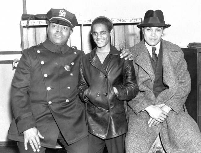 Lino Rivera, 16, is shown in the W. 122nd St. police station on March 20, 1935, with Lieut. S. J. Battle, left, and policeman F.W. Eldridge, right, of the Crime Prevention Bureau. Lino was said by the police to have been the innocent cause of the Harlem riots, for it was a rumor that he had been brutally killed for stealing from a store that brought the mob to 125th Street on the night of March 19.